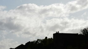 Two girls on top of a castle wall backlit talking and drinking a cloudy afternoon. In La Alcazaba, Malaga, Spain stock footage