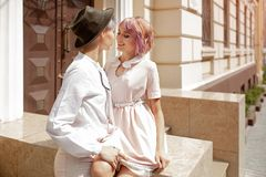 Two girls touching each other near the stairs of the building in the city stock image