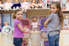Two girls in a toy store with a rows of dolls Royalty Free Stock Photo