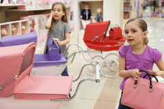 Two girls in a toy store with a rows of dolls Stock Photos