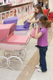 Two girls in a toy store with a rows of dolls Royalty Free Stock Images