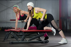 Two girls train in gym with dumbbells Royalty Free Stock Photo