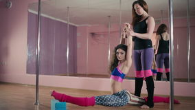 Two girls training in the dance studio. Curly girl foing the splits at the floor. She raise up her hands. The other girl takes the hands of the assistant and stock video footage