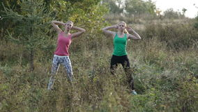Two girls training. Two young girls training together outdoors: body bent exercises stock video