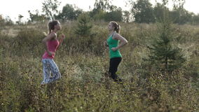 Two girls training. Two young girls training together outdoors: running and jumping exercises stock video footage