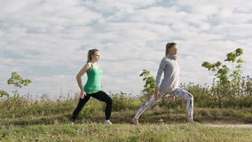 Two girls training. Two young girls training together outdoors: stretching exercises stock video