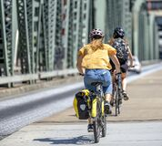 Two girls travel by bike along the pedestrian part of the Hawthorne Bridge, preferring an active healthy lifestyle