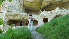 Two girls traveler girlfriend visiting the ancient cave city. Two girls traveler girlfriend visiting the ancient cave city located high in the mountains on a stock footage