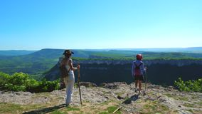 Two girls traveler girlfriend walk on a mountain plateau and admire the amazing views. In the background is a mountain range and a blue sky stock video footage