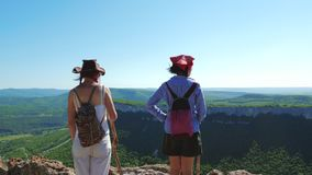 Two girls traveler girlfriend walk on a mountain plateau and admire the amazing views. In the background is a mountain range and a blue sky stock footage