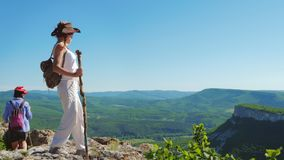 Two girls traveler girlfriend walk on a mountain plateau and admire the amazing views. In the background is a mountain range and a blue sky stock video