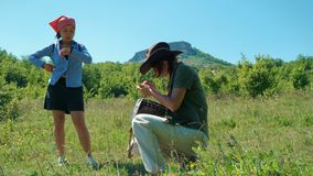 Two girls traveler watch the time on a wristwatch and use a mobile phone to build a route in the mountains. They are surrounded by grass, shrubs, mountains and stock video