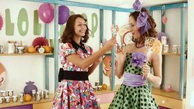 Two girls treat each other with candies. Two girls in bright dresses treat each other with candies stock video