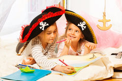 Two girls in tricorns drawing the treasure map Stock Image