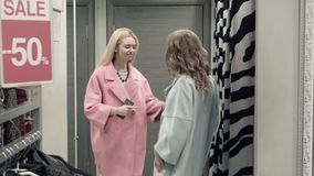 Two girls try on a coat in a locker room. In shop stock video