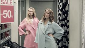 Two girls try on a coat in a locker room. In shop stock footage