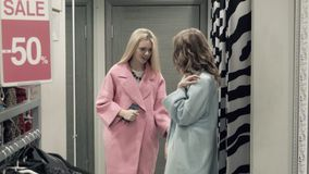 Two girls try on a coat in a locker room. In shop stock video footage