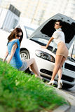 Two girls try to repair the broken car on the road Stock Photo