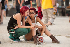 Two girls at Tuborg Green Fest. Two girls at rock festival siting and drinking beer. Photo taken at Tuborg Green Fest 2012 in Bucharest stock photography