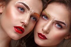 Two girls are twin sisters with an unusual eyebrow makeup. Beauty face. Photo taken in the studio royalty free stock photos