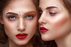 Two girls are twin sisters with an unusual eyebrow makeup. Beauty face. Photo taken in the studio stock images