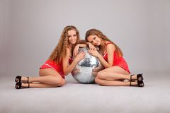 Two girls twins with glitterball on grey Royalty Free Stock Photo