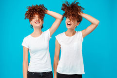 Two girls twins holding hair, joking over blue background. stock photos