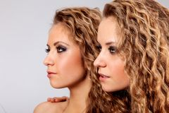 Two girls twins, isolated on the grey background Stock Photo