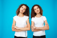 Two girls twins posing with crossed arms over blue background. Stock Images