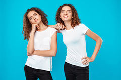 Two girls twins posing over blue background. One displeased, another smiling. Stock Photography