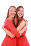 Two girls twins in red dresses hugging stock images