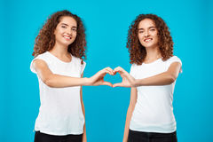 Two girls twins showing heart with hands over blue background. Royalty Free Stock Image