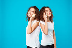 Two girls twins speaking on phones, smiling over blue background. Stock Photo