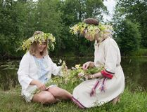 Two girls is twist flowers into a wreath. Two girls is twine a wreath of flowers at meadow royalty free stock photography