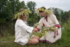 Two girls is twist flowers into a wreath. Two girls traditional clothes is twine a wreath of flowers against lake stock image