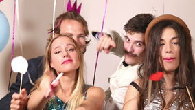 Two girls and two guys playing with props in party photo booth. Two beautiful girls and two handsome guys playing with props in party photo booth stock video
