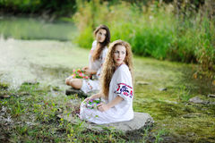 Two girls in Ukrainian shirts. Are on the background of the river stock photos