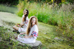 Two girls in Ukrainian shirts are on the background of the river Royalty Free Stock Image