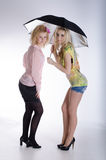 Two girls under black umbrella Stock Image
