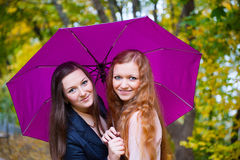 Two girls under umbrella in autumn park Stock Photos