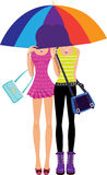 Two girls under the umbrella of the rainbow color Royalty Free Stock Photos