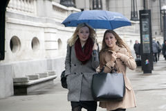Two girls under an umbrella on a rainy day cross the road Stock Photos