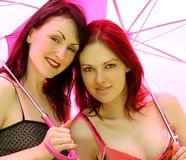 Two girls under umbrellas Royalty Free Stock Photography