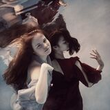 Two girls underwater in a blue and red dress