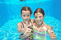 Two girls underwater in swimming pool