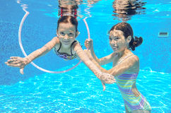 Two girls underwater in swimming pool Royalty Free Stock Photos
