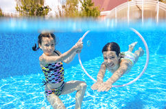 Two girls underwater in swimming pool. Happy active kids play underwater in swimming pool, girls diving and having fun, children on summer vacation, sport royalty free stock photos