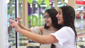 Two girls use the interactive panel in the mall. girls choose the goods with the help of an interactive panel. Two beautiful girls use the interactive panel in stock video footage