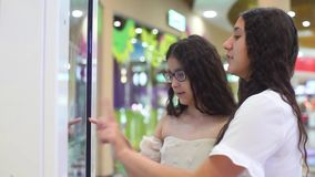 Two girls use the interactive panel to make a purchase at the mall. Two young girls use the interactive panel to make a purchase at the mall stock video