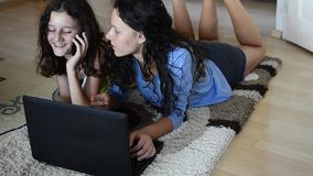 Two girls using laptop and having fun. Wireless Technology, Two sister girls use laptop laying, having fun and joy for finishing successful project stock video footage